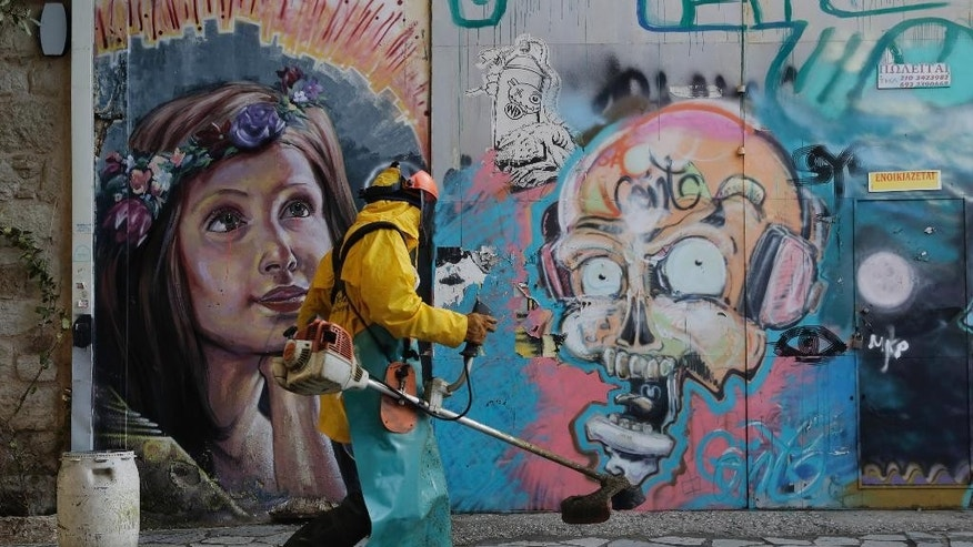 A municipality worker carries a grass cutter in front of graffitied wall in central Athens, on Wednesday, Feb. 25, 2015. Greece cleared a major hurdle on Tuesday after the finance ministers of the other 18 eurozone countries approved a list of policy goals Greek Finance Minister Yanis Varoufakis sent to Brussels and granted the four-month bailout extension. The list is being used as a starting point for the creation of new measures Greek parliament will have to vote into law.(AP Photo/Petros Giannakouris)