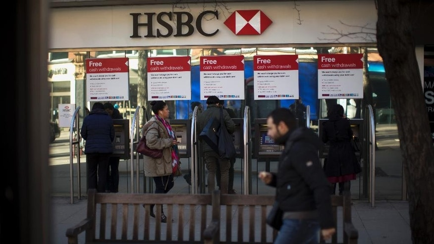 "FILE - This is a  Wednesday, Feb. 18, 2015  file photo of people as they use ATM machines outside a branch of HSBC in London. HSBC executives offered a fresh mea culpa Monday Feb. 23, 2015 as its chief executive found himself personally mired in the scandal surrounding allegations that the bank helped wealthy clients dodge taxes. Europe's biggest bank by market value said past practices at its Swiss private bank were ""unacceptable"" as it posted 2014 net income that fell 16 percent to $13.7 billion. Meanwhile, Britain's Guardian newspaper reported that Chief Executive Officer Stuart Gulliver had an account at the same unit. (AP Photo/Matt Dunham)"