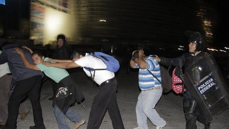 Protesters are taken into custody by police during their protest to demand better labor conditions for teachers in Acapulco, Mexico, late Tuesday, Feb. 24, 2015. Police clashed with union members representing teachers and other public workers who were blocking the airport. Demonstrators also protested the Sept. 26, 2014 disappearance of 43 students in Guerrero state. (AP Photo/Bernandino Hernandez)
