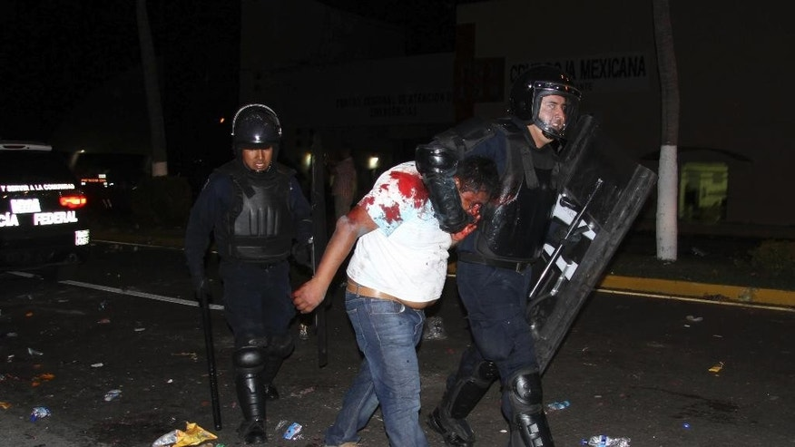 An injured protester is taken into custody by police during a protest demanding better labor conditions for teachers in Acapulco, Mexico, late Tuesday, Feb. 24, 2015. Police clashed with union members representing teachers and other public workers who were blocking the airport. Demonstrators also protested the Sept. 26, 2014 disappearance of 43 students in Guerrero state. (AP Photo/Bernandino Hernandez)