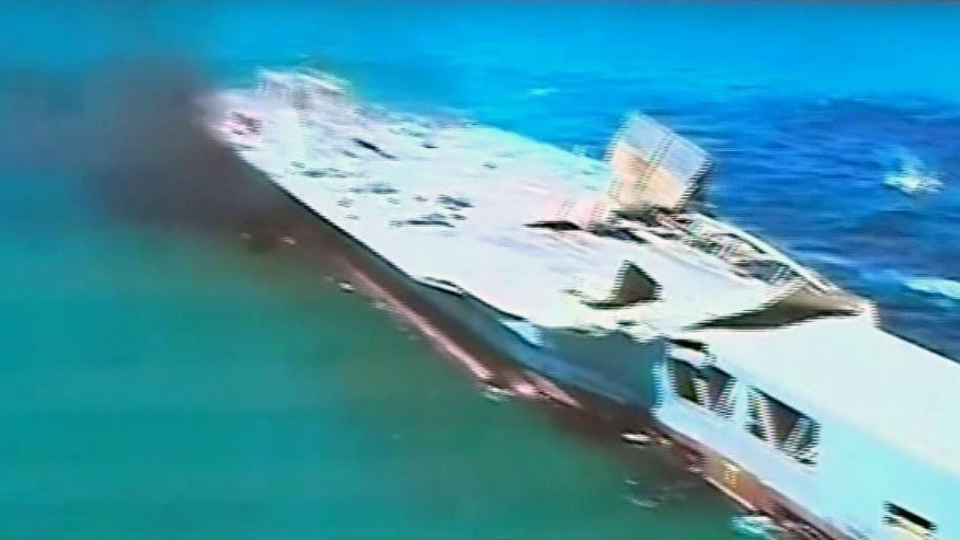 "This image taken from Iranian state TV, shows footage of damage to a mock U.S. aircraft carrier during large-scale naval and air defense drills by Iran's Revolutionary Guard, near the Strait of Hormuz, Iran, Wednesday, Feb. 25, 2015. The drill, named Great Prophet 9, was the first to involve a replica of a U.S. carrier. Cmdr. Kevin Stephens, the spokesman for the U.S. Navy's 5th Fleet in Bahrain, said they were monitoring the drills, but downplayed the simulated attack on the carrier, saying the U.S. military was ""not concerned about this exercise.""(AP Photo/Iran TV)  TV OUT"