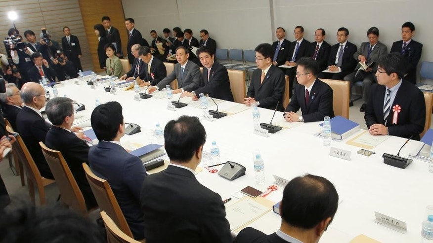 Japanese Prime Minister Shinzo Abe, fourth from right, speaks at a meeting with a panel of experts at his official residence in Tokyo, Wednesday, Feb. 25, 2015. The panel of experts appointed by Abe met for the first time Wednesday to discuss what he should say in a statement marking the 70th anniversary of the end of World War II, fueling speculation that he may water down previous government apologies for the country's wartime past. (AP Photo/Shizuo Kambayashi)