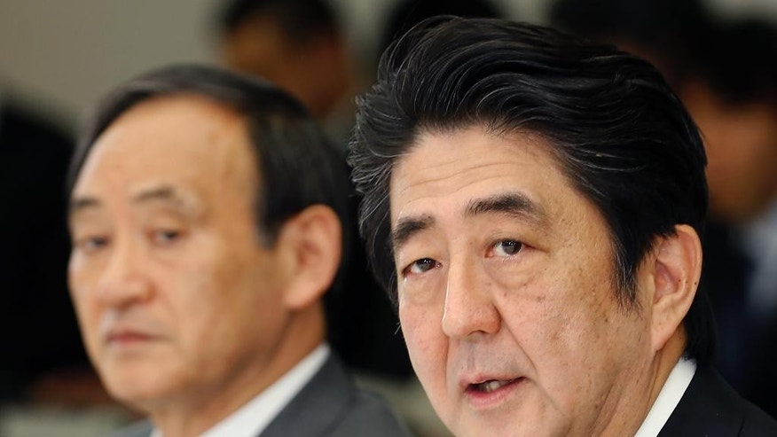 Japanese Prime Minister Shinzo Abe, right, speaks at a meeting with a panel of experts at his official residence in Tokyo, Wednesday, Feb. 25, 2015. The panel of experts appointed by Abe met for the first time Wednesday to discuss what he should say in a statement marking the 70th anniversary of the end of World War II, fueling speculation that he may water down previous government apologies for the country's wartime past. Second from right is government spokesman Chief Cabinet Secretary Yoshihide Suga. (AP Photo/Shizuo Kambayashi)