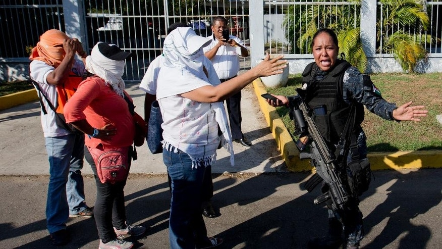 In this Feb. 10, 2015 photo, masked teachers confront a police officer during a protest to bring attention to the case of the disappearance of 43 students from the Isidro Burgos rural teachers college, in Acapulco, Mexico. Mexico's President Enrique Pena Nieto took heat for the government's handling of the September disappearance of 43 college students, allegedly at the hands of police in Guerrero state who handed them over to be killed by a drug cartel. The case highlighted ties between local authorities and organized criminals, as well as the administration's inability to defuse public anger over the crime. (AP Photo/Eduardo Verdugo)