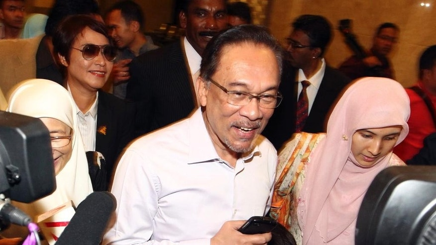 FILE - In this Tuesday, Feb. 10, 2015 file photo, Malaysian opposition leader Anwar Ibrahim, center, arrives at court house in Putrajaya, Malaysia. Ibrahim began a 5-year prison sentence on Feb. 10 after being found guilty of sodomizing a former male aide in 2008. (AP Photo/File) MALAYSIA OUT