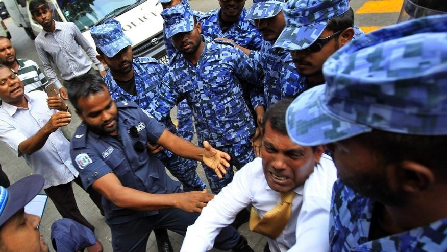 FILE - In this Monday, Feb. 23, 2015, photo, Maldives former President and current opposition leader Mohamed Nasheed, in white, tussles with policemen who stopped him from speaking to journalists in Male, Maldives, Monday, Feb. 23, 2015. Authorities arrested Nasheed on Sunday, ordering him to stand trial for his 2012 decision to arrest a senior judge. (AP Photo/Sinan Hussain, File)