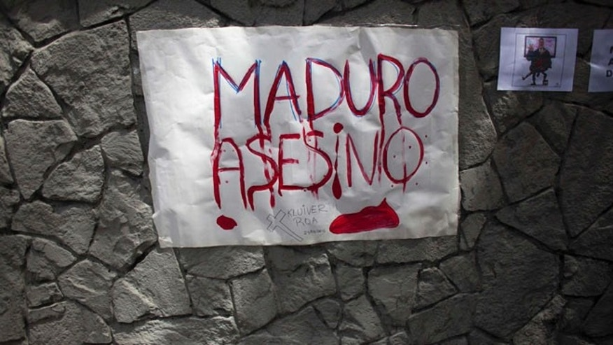 "A sign placed by protesters reads in Spanish ""Maduro assassin,"" referring to President Nicolas Maduro, outside the Vatican's diplomatic mission in Caracas, Venezuela, Wednesday, Feb. 25, 2015. Protesters gathered here to ask Pope Francis to intervene after the death of a 14-year-old boy who was shot in the head Tuesday at an anti-government protest in the city of San Cristobal. (AP Photo/Ariana Cubillos)"