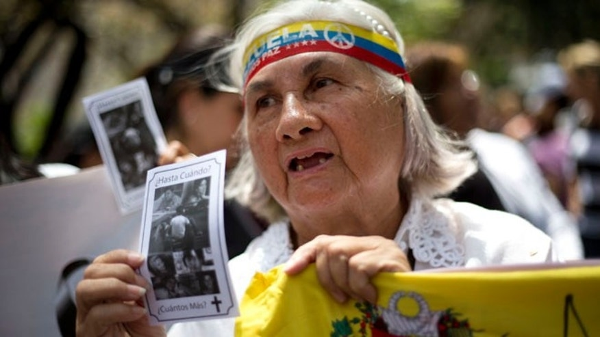 A woman holds up a picture of people who have died during anti-government protests as she stands outside the Vatican's diplomatic mission in Caracas, Venezuela, Wednesday, Feb. 25, 2015. Protesters gathered here to ask Pope Francis to intervene after the Tuesday death of a 14-year-old boy who was shot in the head during an anti-government protest in the city of San Cristobal. (AP Photo/Ariana Cubillos)