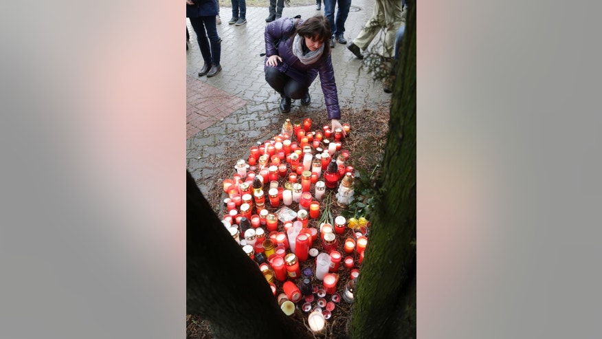 A woman places a candle to pay respect to victims of the shooting in Uhersky Brod, Czech Republic, Wednesday, Feb. 25, 2015. On Tuesday a gunman opened fire in a restaurant killing eight people and seriously wounding a woman before he fatally shot himself. (AP Photo/Petr David Josek)