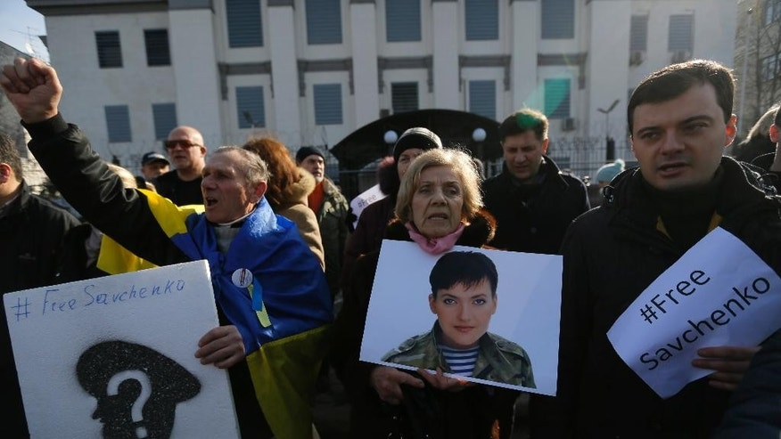 A woman holds a picture of Ukrainian pilot Nadezhda Savchenko during a rally outside the Russian Embassy in Kiev, Ukraine, Tuesday, Feb. 24, 2015. Ukrainian pilot Nadezhda Savchenko was captured by Russia-backed rebels during fighting in eastern Ukraine. The Kiev government has so far been unsuccessful in seeking the extradition of Savchenko who was elected a member of the Ukrainian parliament in the October 2014 Ukrainian parliamentary election. (AP Photo/Sergei Chuzavkov)