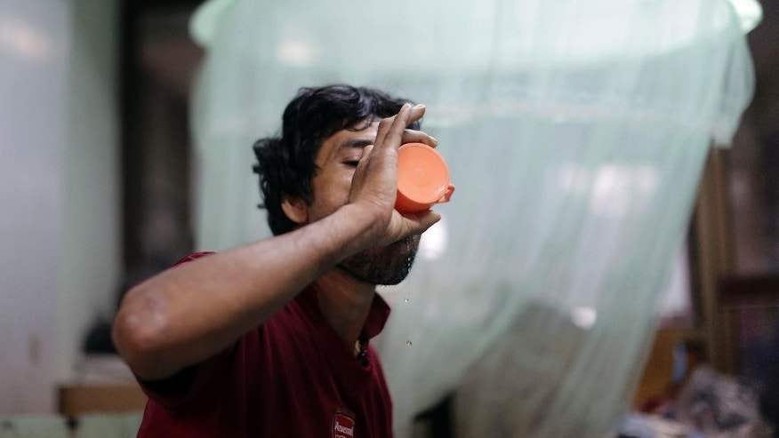 In this Friday, Dec. 12, 2014 photo, Min Min, from Myanmar, consumes a vitamin drink. Min is just one of countless hidden casualties of the international demand for cheap fish. (AP Photo/Wong Maye-E)