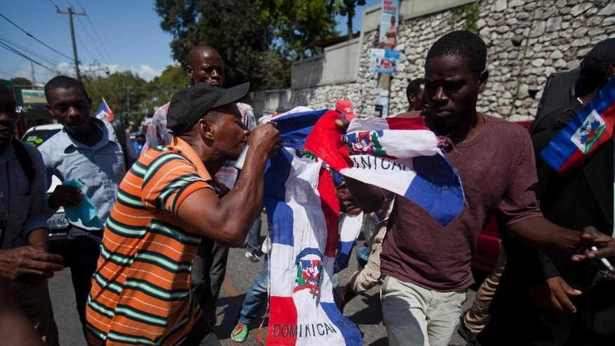 A protester uses his teeth to rip apart a Dominican national flag, during an anti-Dominican Republic protest in Port-au-Prince, Haiti, Wednesday, Feb. 25, 2015. Protesters outraged over a Feb. 11 lynching of young man of Haitian descent in the Dominican city of Santiago are demanding that the neighboring country respect the human rights of Haitians. (AP Photo/Dieu Nalio Chery)