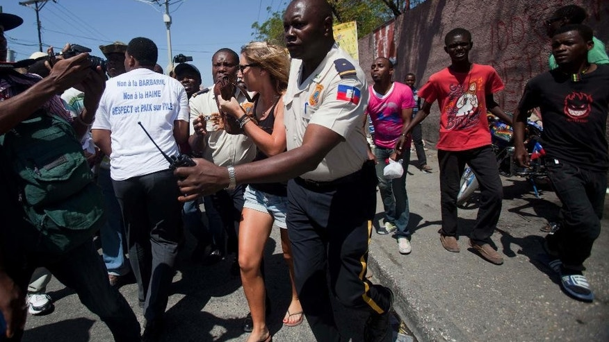 Haitian Police officers protectively escort a woman to a waiting car, as protesters pursue them shouting that she is Dominican, during an anti-Dominican Republic protest in Port-au-Prince, Haiti, Wednesday, Feb. 25, 2015. Protesters outraged over a Feb. 11 lynching of a young man of Haitian descent in the Dominican city of Santiago are demanding that the neighboring country respect the human rights of Haitians. (AP Photo/Dieu Nalio Chery)