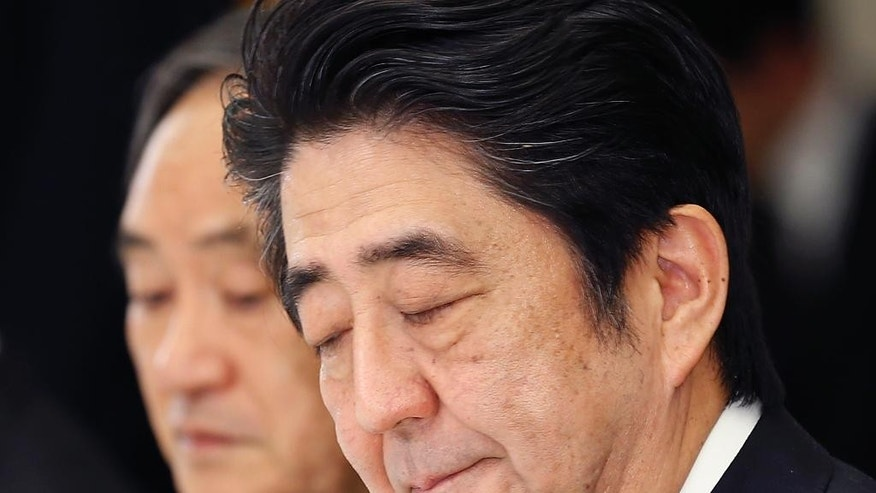 In this Wednesday, Feb. 25, 2015 photo, Japanese Prime Minister Shinzo Abe bites his lips during a meeting with a panel of experts at his official residence in Tokyo. Abe convened the experts to advise him on what to say to mark the 70th anniversary of the end of World War II on Aug. 15. A tug-of-war has emerged between those who want Abe to stick to the apologies made by past prime ministers for Japan's wartime aggression and colonial rule, and those who say such accounts are exaggerated or even fabricated. Abe, known for harboring revisionist views, must strike a balance, as any statement viewed as watering down past apologies would anger China and South Korea and displease the United States too. Behind Abe is government spokesman Chief Cabinet Secretary Yoshihide Suga. (AP Photo/Shizuo Kambayashi)