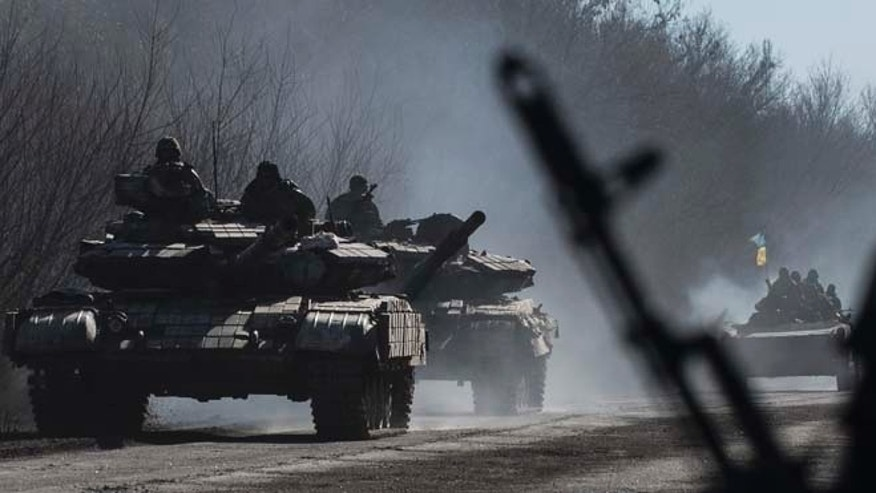 Feb. 24, 2015: Ukrainian troops ride on tanks near Artemivsk, eastern Ukraine. Ukrainian officials said they havent yet started pulling heavy weapons back from a frontline in eastern Ukraine because of continued rebel violations of a cease-fire deal.