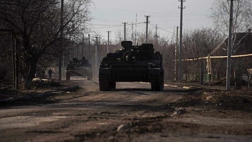 Ukrainian armored vehicles drive near the village of Luhanske, eastern Ukraine, Tuesday, Feb. 24, 2015. Ukrainian officials said they haven't yet started pulling heavy weapons back from a frontline in eastern Ukraine because of continued rebel violations of a cease-fire deal. (AP Photo/Evgeniy Maloletka)