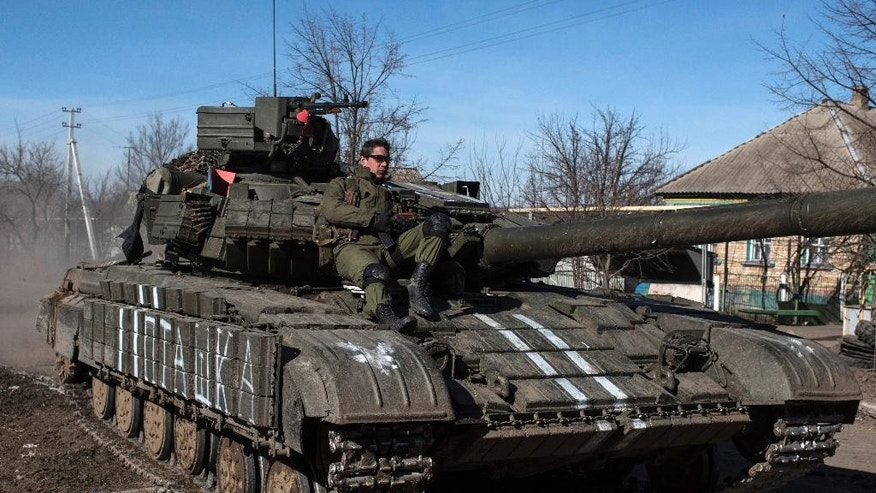 Ukrainian troops ride on a tank near the village of Luhanske, eastern Ukraine, Tuesday, Feb. 24, 2015. Ukrainian officials said they haven't yet started pulling heavy weapons back from a frontline in eastern Ukraine because of continued rebel violations of a cease-fire deal. (AP Photo/Evgeniy Maloletka)