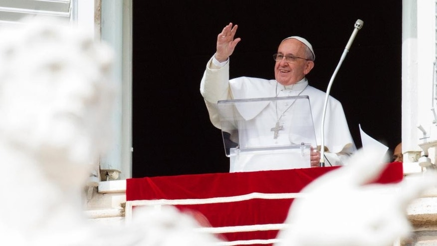 Pope Francis waves to faithful from his studio window overlooking St. Peter's Square, during the Angelus noon prayer at the Vatican, Sunday, Feb. 22, 2015. Francis told tens of thousands of Romans, tourists and pilgrims in St. Peter's Square that later Sunday he and top aides were starting a spiritual renewal retreat. Until Friday morning, they will spend time listening to reflections, meditating and praying in Ariccia, a Rome suburb. (AP Photo/Riccardo De Luca)