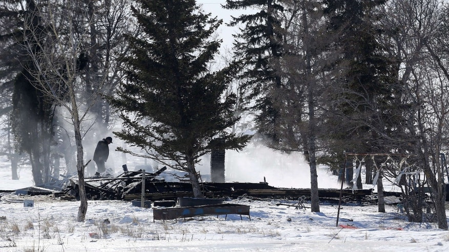 Feb. 25, 2015: Responders and investigators work at the scene of a fatal house fire near the rural community of Kane, Manitoba.