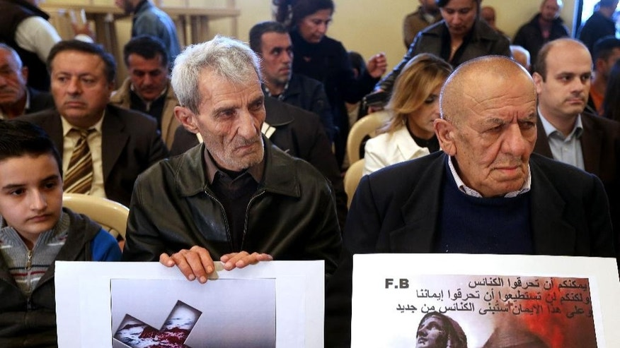 "Assyrians citizens hold placards during a sit-in for abducted Christians in Syria and Iraq, at a church in Sabtiyesh area east Beirut, Lebanon, Thursday, Feb. 26, 2015. Islamic State militants snatched more hostages from homes in northeastern Syria over the past three days, bringing the total number of Christians abducted to over 220 in the one the largest hostage-takings by the extremist group, activists said Thursday. Arabic on the placard, right, reads, ""you can burn the churches but you cannot burn our faiths, and in this faith we will rebuild the churches."" (AP Photo/Hussein Malla)"