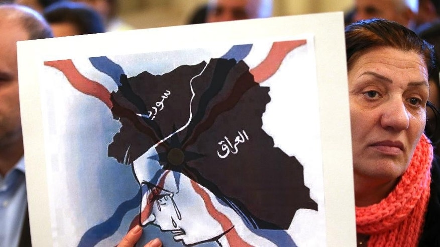 An Iraqi Assyrian woman who fled from Mosul to Lebanon holds a placard depicting the map of Iraq and Syria, during a sit-in for abducted Christians in Syria and Iraq, at a church in Sabtiyesh area east Beirut, Lebanon, Thursday, Feb. 26, 2015. Islamic State militants snatched more hostages from homes in northeastern Syria over the past three days, bringing the total number of Christians abducted to over 220 in the one the largest hostage-takings by the extremist group, activists said Thursday. (AP Photo/Hussein Malla)