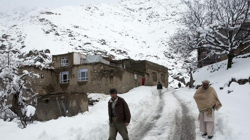 Afghan men walk in a village close to an avalanche site in Panjshir province north of Kabul, Afghanistan, Wednesday, Feb. 25, 2015. Avalanches caused by a heavy winter snow killed at least 124 people in northeastern Afghanistan, an emergency official said Wednesday, as rescuers clawed through debris with their hands to save those buried beneath. (AP Photo/Massoud Hossaini)