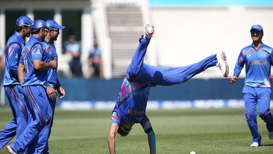 Afghanistan's Hamid Hassan is watched by his teammates as he performs a hand-stand after taking a catch to dismiss Scotland's Josh Davey during their Cricket World Cup Pool A match in Dunedin, New Zealand, Thursday, Feb. 26, 2015. (AP Photo/Dianne Manson)