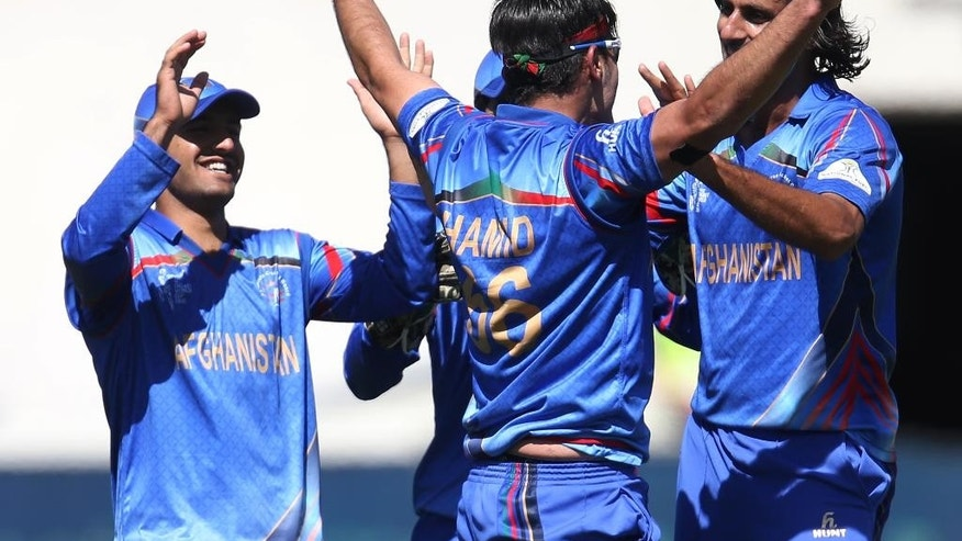 Afghanistan's Hamid Hassan is congratulated by teammates reacts after taking a catch to dismiss Scotland's Josh Davey during their Cricket World Cup Pool A match in Dunedin, New Zealand, Thursday, Feb. 26, 2015. (AP Photo/Dianne Manson)