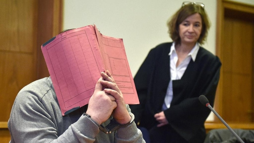 Former nurse, only identified as Niels H., hides his face behind a folder next to his lawyer Ulrike Baumann at the local court in Oldenburg, Germany, Thursday, Feb. 26, 2015. The court found the 38-year-old guilty of charges including two counts of murder, and two counts of attempted murder and sentenced him to life in prison. (AP Photo/dpa, Carmen Jaspersen)