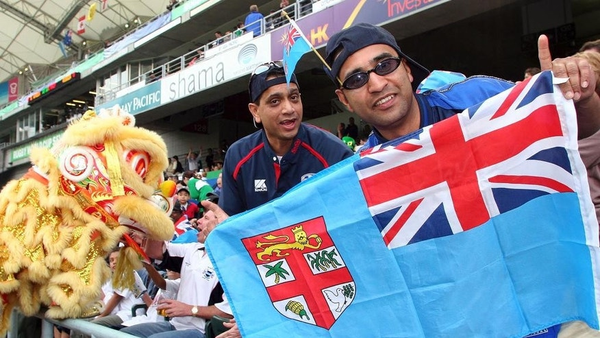 FILE - In this Friday, March 18, 2005, file photo, rugby fans hold a Fiji national flag during the Rugby World Cup Sevens in Hong Kong. Fiji Prime Minister Voreqe Bainimarama announced Friday, Feb. 27, 2015, the Pacific island nation is launching a two-month competition to find the best design for a new flag. (AP Photo/Water Chan, File)