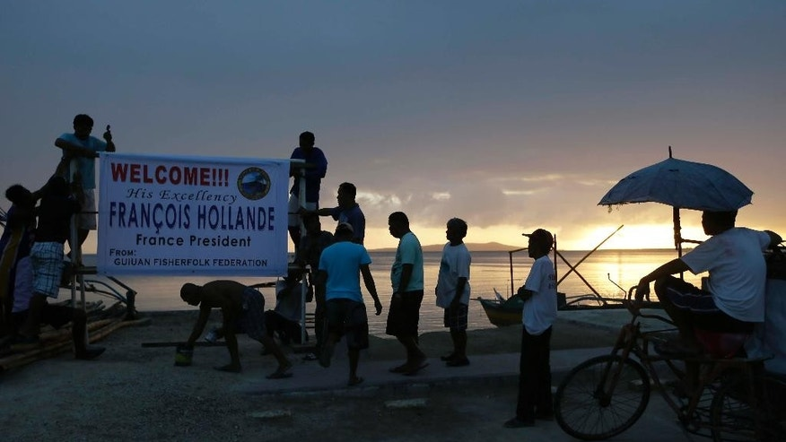 Fisherfolk install a tarpaulin to welcome Friday's visit of French President Francois Hollande at sunset in the typhoon-ravaged Guiuan township, Eastern Samar province, central Philippines, Thursday, Feb. 26, 2015. Hollande arrived Thursday for a two-day state visit which is expected to focus on climate change. (AP Photo/Bullit Marquez)