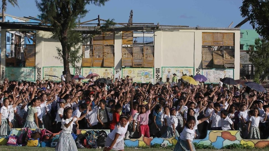 With their damaged school building in the background, schoolchildren of Guiuan East Central School rehearse their number in preparation for Friday's visit of French President Francois Hollande Thursday, Feb. 26, 2015 at the typhoon-ravaged Guiuan township, Eastern Samar province in central Philippines. Hollande arrived Thursday for a two-day state visit which is expected to focus on climate change.  (AP Photo/Bullit Marquez)
