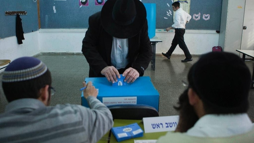 FILE - In this Jan. 22, 2013 file photo, an Israeli Jewish settler votes in the settlement of Emanuel in the West Bank, during legislative elections. With few exceptions, Israel does not allow absentee voting. But when the country goes to the polls next month, hundreds of thousands of West Bank settlers will be casting votes, even though they do not reside in sovereign Israeli territory. (AP Photo/Dan Balilty, File)