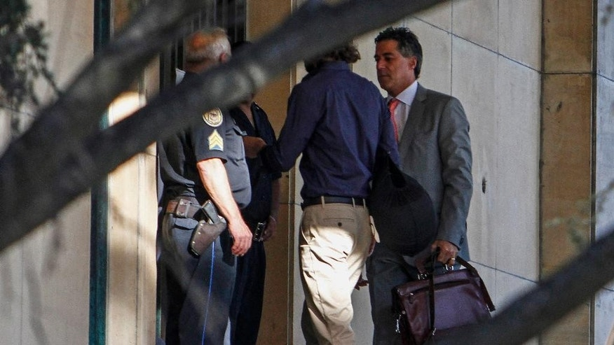 This Feb. 23, 2015 photo shows, through tree branches, Federal Judge Daniel Rafecas, right, arriving to the federal court house in Buenos Aires, Argentina. On Thursday, Feb. 26, 2015, Rafecas dismissed prosecutor Alberto Nisman's allegations that President Cristina Fernandez tried to cover-up the alleged involvement of Iranian officials in the 1994 bombing of a Jewish center in Buenos Aires. (AP Photo/Agustin Marcarian)