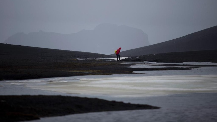 "In this Jan. 24, 2015 photo, an international scientist collects samples in Deception Island, in the South Shetland Islands archipelago Antarctica. Parts of Antarctica are melting so rapidly it has become ""ground zero of global climate change without a doubt,"" said Harvard geophysicist Jerry Mitrovica. (AP Photo/Natacha Pisarenko)"