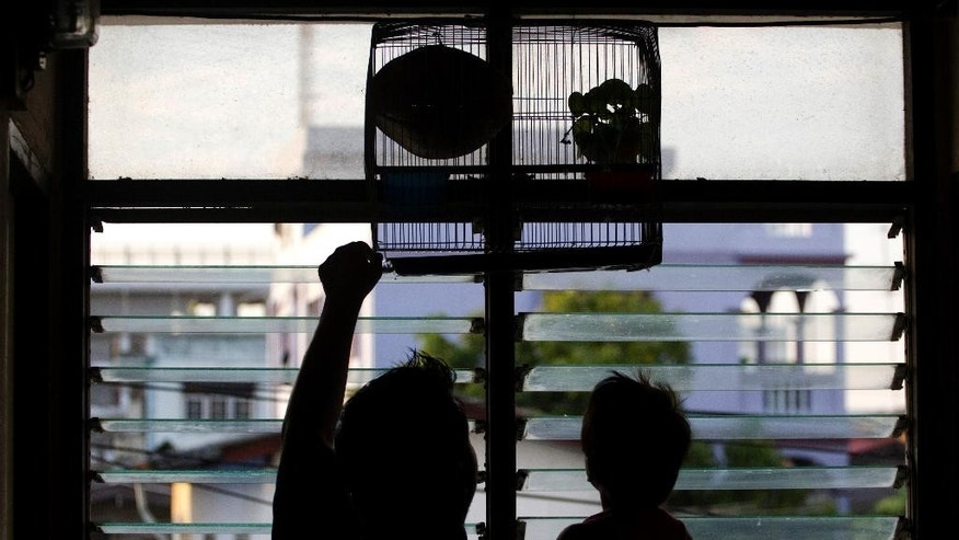 In this Jan. 12, 2015, photo, an asylum-seeker and his niece play with a bird in a cage at an apartment building on the outskirts of Bangkok, Thailand.  More than half the 14 million refugees and asylum-seekers under the mandate of the U.N. refugee agency do not live in camps; a growing number of them live in urban areas. (AP Photo/Sakchai Lalit)