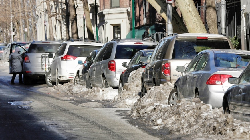 Some snow-bound cars line one side of a street in New York's Upper West Side neighborhood, Wednesday, Feb. 25, 2015. For the first time in weeks, New York City's alternate side parking rules are back in place after being suspended to allow for snow removal. (AP Photo/Richard Drew)