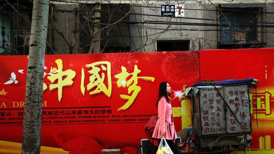 "A woman carries a bag of groceries as she walks past a Chinese government billboard stating ""China Dream"" near a residential building in Beijing, on Thursday, Feb. 26, 2015. Since taking the reins of the ruling Communist Party in 2012, President Xi Jinping has leveraged slogans to promote his program of strengthening party rule, cracking down on corruption and building up China's international standing. The most famous of these has been the Chinese Dream, a fuzzy concept that seeks to motivate the nation's 1.3 billion people to realize prosperity, happiness and their rightful place on the world stage. (AP Photo/Andy Wong)"