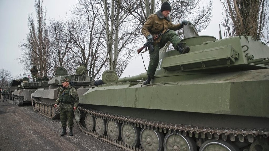 Russia-backed separatist fighters stand on self propelled 152 mm artillery pieces, part of a unit moved away from the front lines, in Yelenovka, near Donetsk, Ukraine,Thursday, Feb. 26, 2015. Russia's foreign minister is sharply criticizing Ukraine's insistence that it won't begin pulling back heavy weapons in its fight against separatists in the east until the rebels fully observe a cease-fire. (AP Photo/Vadim Ghirda)