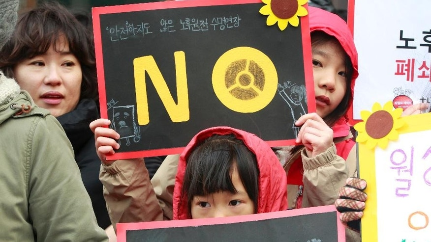 In this Thursday, Feb. 26, 2015, photo, elementary school students attend a rally against nuclear power plants near the government complex in Seoul, South Korea. The Nuclear Safety and Security Commission said Friday, Feb. 27 that seven of nine commissioners voted to approve to restart the Wolsong No. 1 reactor located in Gyeongju city, 275 kilometers (170 miles) south of Seoul. It was South Korea's first such decision since the meltdowns at Japan's Fukushima Daiichi reactors in 2011 raised safety concerns.  (AP Photo/Ahn Young-joon)