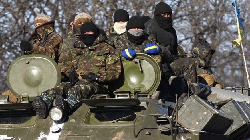 Feb. 17, 2015: Ukrainian government soldiers sit on top of their armored vehicle driving on a road stretching away from the town of Artemivsk, Ukraine, towards Debaltseve. (AP)