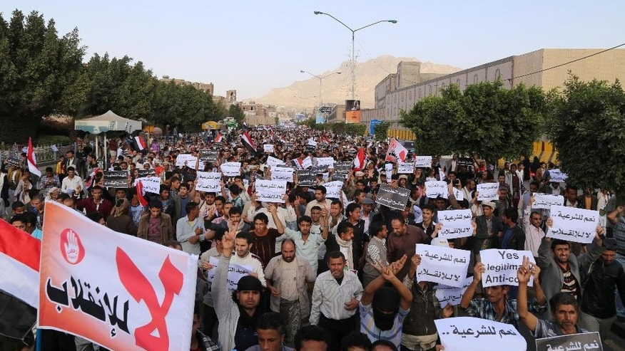 "Protesters march during an anti-Houthi demonstration in Sanaa, Yemen, Wednesday, Feb. 25, 2015. Arabic writing on a banner at bottom left that reads,""no to the coup."" and the other banners read ""yes to legitimacy, no to the coup."" A group of oil-rich Arab Gulf countries threw their support behind Yemen's embattled president Wednesday as the group's chief visited Abed Rabbo Mansour Hadi in a southern port city he fled to amid the Shiite rebel power grab in the capital, Sanaa. (AP Photo/Nadia Abdullah)"