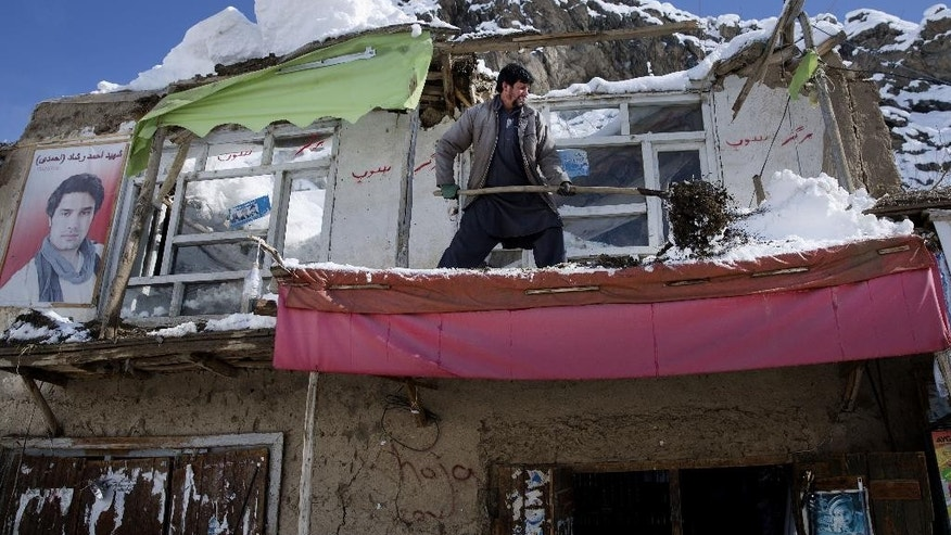 An Afghan villager cleans off snow after the rooftop of his home was damaged from an avalanche, in the Khanj district of Panjshir province, north of Kabul, Afghanistan, Thursday, Feb. 26, 2015. The number of people killed in a massive avalanche in a mountain-bound valley in northeastern Afghanistan rose on Thursday to more than 160 as lack of equipment and the sheer depth of snow that buried entire homes and families hampered rescue efforts. (AP Photo/Massoud Hossaini)