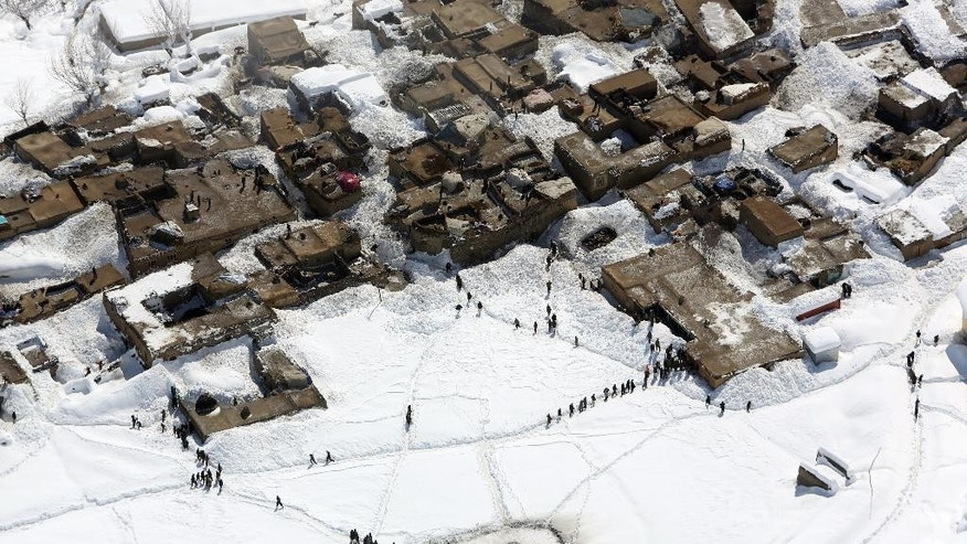 Survivors wait to receive food donations near the site of an avalanche in the Paryan district of Panjshir province, north of Kabul, Afghanistan, Friday, Feb. 27, 2015. The death toll from severe weather that caused avalanches and flooding across much of Afghanistan has jumped to more than 200 people, and the number is expected to climb with cold weather and difficult conditions hampering rescue efforts, relief workers and U.N. officials said Friday. (AP Photo/Rahmat Gul)