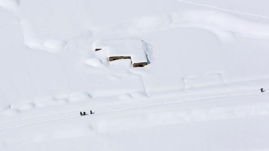 A house is covered with snow from an avalanche in the Paryan district of Panjshir province, north of Kabul, Afghanistan, Friday, Feb. 27, 2015. The death toll from severe weather that caused avalanches and flooding across much of Afghanistan has jumped to more than 200 people, and the number is expected to climb with cold weather and difficult conditions hampering rescue efforts, relief workers and U.N. officials said Friday. (AP Photo/Rahmat Gul)