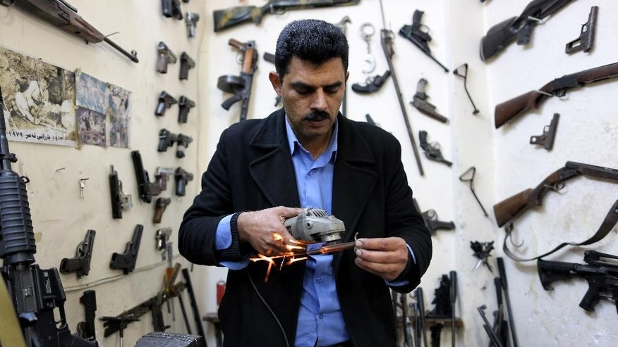 In this Wednesday, Feb. 25, 2015 photo, gunsmith Bahktiyar Sadr-Aldeen repairs a weapon at his shop, in Irbil, northern Iraq. Sadr-Aldeen doesn't limit his work to his shop. Sometimes he goes out to the front lines himself, mostly to repair heavy weapons that can't be transported. The peshmerga send a car and take him out to the front to do his work. (AP Photo/Bram Janssen)