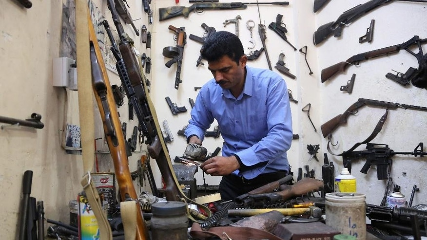 In this Wednesday, Feb. 25, 2015 photo, gunsmith Bahktiyar Sadr-Aldeen repairs a weapon at his shop, in Irbil, northern Iraq. Sadr-Aldeen, an Iraqi Kurd, has seen his business shoot up by 50 percent since last June, when the Islamic State took over the Iraqi city of Mosul. The Kurdish fighting force known as the pershmerga has been at war against the Sunni extremists ever since, keeping Aldeen busy. (AP Photo/Bram Janssen)