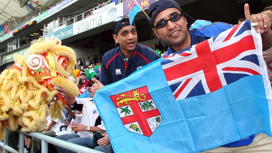 March 18, 2005: Rugby fans hold a Fiji national flag during the Rugby World Cup Sevens in Hong Kong.