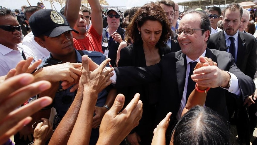 French President Francois Hollande, front right, is greeted by the crowd during his visit to the typhoon-ravaged Guiuan township, Eastern Samar province in central Philippines Friday, Feb. 27, 2015. Hollande on Friday took his warning about the need for funds for a landmark climate deal to a central Philippine town that was devastated by a killer typhoon in 2013. (AP Photo/Bullit Marquez)