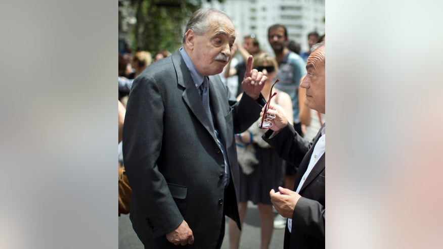 FILE - In this Jan. 11, 2015 file photo, Argentina's former judge Julio Cesar Strassera, left, speaks with France's ambassador to Argentina, Jean-Michel Casa, during a demonstration in solidarity with the victims of an attack in Paris, outside France's embassy in Buenos Aires, Argentina. Strassera, prosecutor in the trial that saw the conviction of Argentina's military dictatorship leaders, died in Buenos Aires on Friday, Feb. 27, 2015. He was 81. Strassera died in the clinic San Camilo de Buenos Aires where he had been admitted for a respiratory illness. (AP Photo/Rodrigo Abd, File)